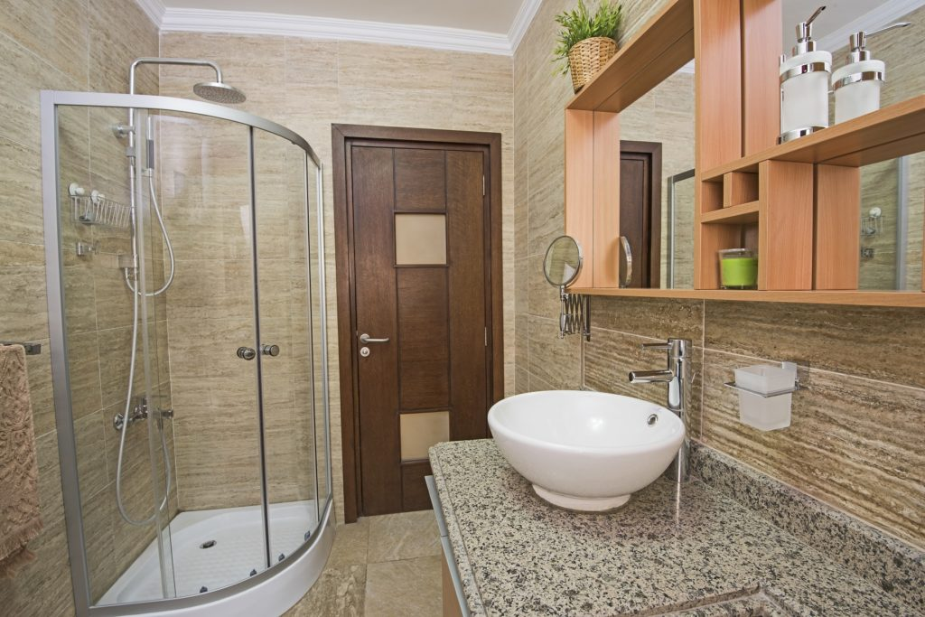Interior design of a redone bathroom with shower doors encasing a shower cubicle
