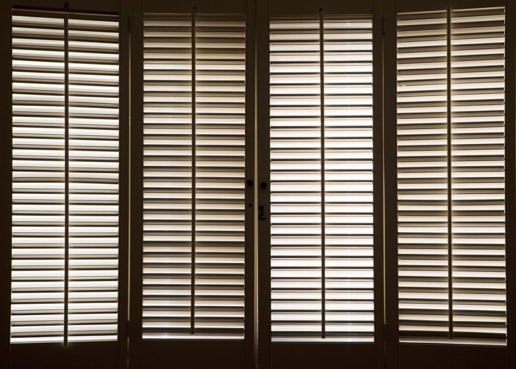 Wood blinds in front of bright, sunlit windows